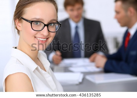 Portrait of a young business woman against a group of business people at a meeting. - stock photo