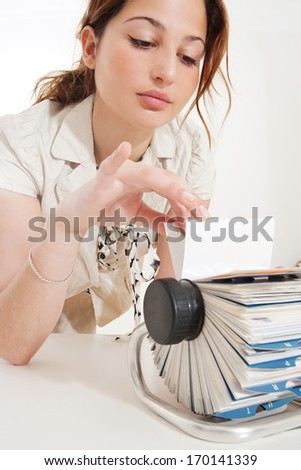 Portrait of a young business woman flicking through her clients contact details database on her roller deck with her fingers while at her working desk, picking a card. Office interior. - stock photo