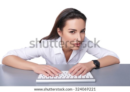 Portrait of a young business woman leaning against a keyboard peeking at camera, isolated on white.
