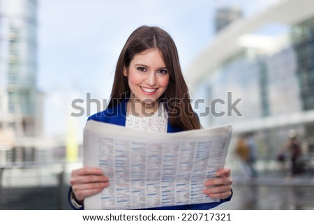Portrait of a young business woman reading a newspaper - stock photo