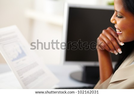 Portrait of a young business woman reading documents - stock photo