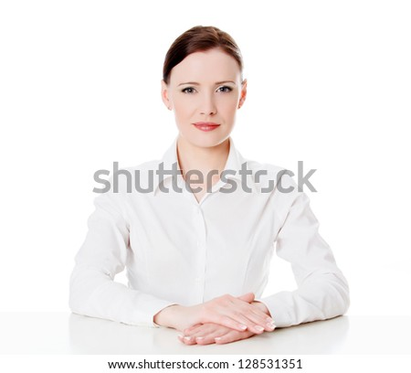 Portrait of a young business woman sitting at a white table, isolated on white - stock photo