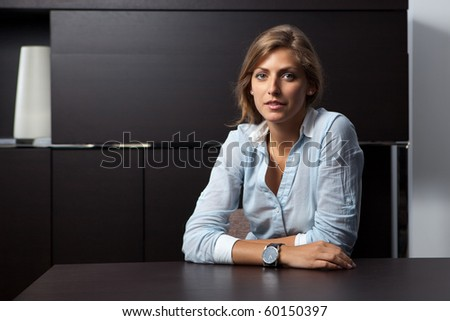 Portrait of a young business woman sitting at office table looking at the camera - stock photo