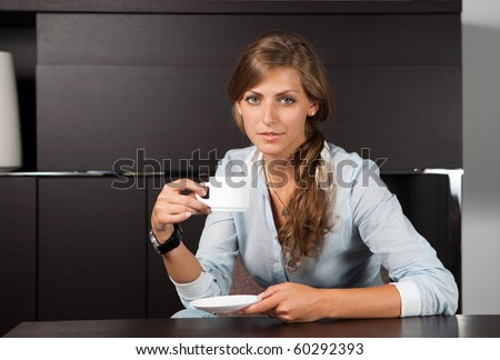 Portrait of a young business woman sitting at office table with cup of coffee looking at the camera - stock photo