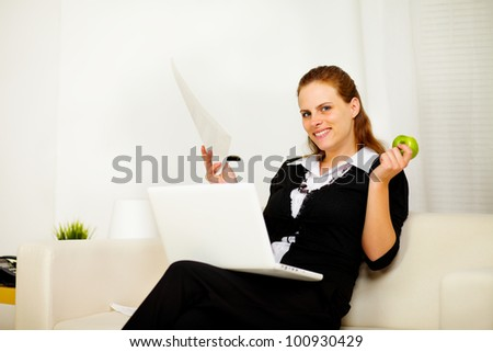 Portrait of a young business woman smiling and working at home while looking at you - stock photo