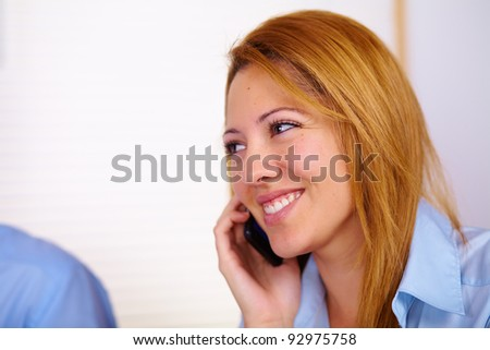 Portrait of a young business woman talking on mobile phone.