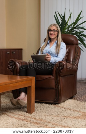 Portrait Of A Young Business Woman Using A Touchpad In The Office