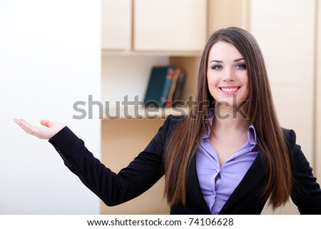 Portrait of a young business woman. with her hand outstretched, as though she is presenting something.