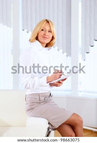 portrait of a young business woman with papers in the office