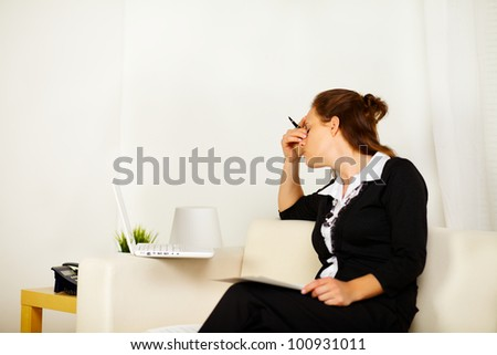 Portrait of a young business woman working at home with fatigue and stress - stock photo
