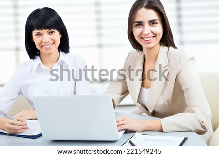 Portrait of a young business women using laptop at office - stock photo