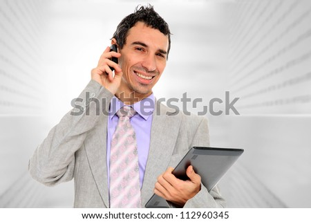 Portrait of a  young businessman, at corporate using a tablet pc and talking on the phone