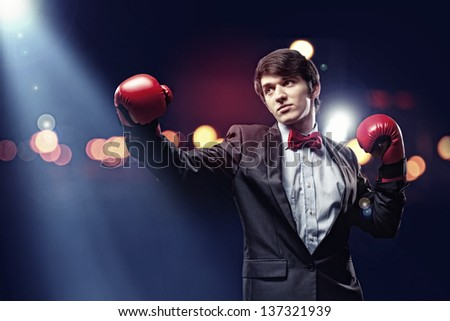Portrait of a young businessman boxing. conceptual collage - stock photo