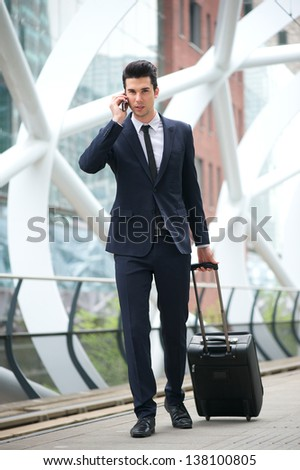Portrait of a young businessman calling on phone and traveling with bag at metro station - stock photo
