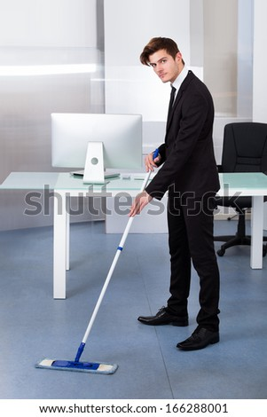 Portrait Of A Young Businessman Cleaning Office With Mop - stock photo
