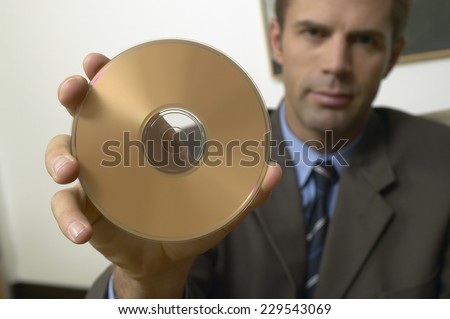 Portrait of a young businessman displaying a CD in lounge setting