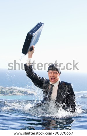 Portrait of a young businessman going out of the water with a briefcase in a swimming pool - stock photo