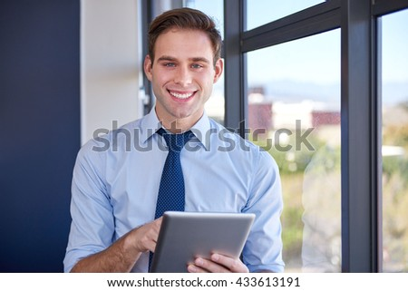 Portrait of a young businessman holding a digital tablet next to large windows in his office, smiling confidently at the camera 