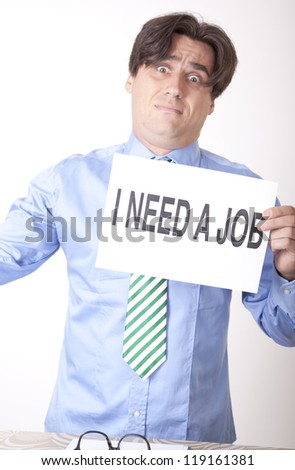 Portrait of a young businessman holding a sign need a job.