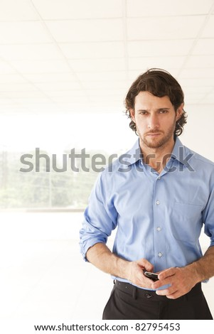 portrait of a young businessman holding his cell phone - stock photo