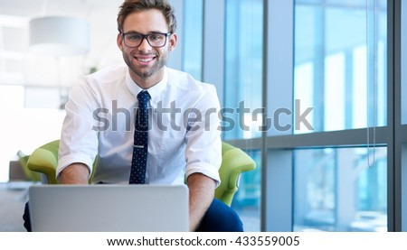 Portrait of a young businessman in a modern office space, typing on his laptop in front of him, and smiling confidently at the camera - stock photo