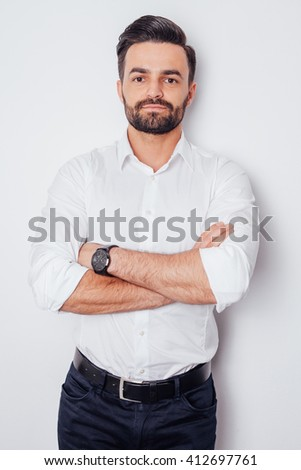 Portrait of a young businessman in a white shirt with arms crossed - stock photo