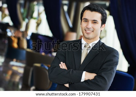 Portrait of a young businessman in suit standing at hotel interior - stock photo