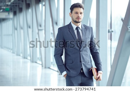 Portrait of a  young businessman in suit standing at office - stock photo