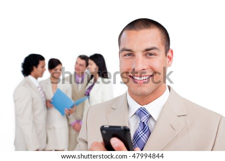 Portrait of a young businessman looking at his cellphone in front of his team - stock photo