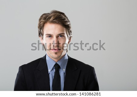 Portrait of a young businessman on grey background looking directly at camera - stock photo