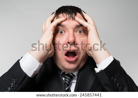 portrait of a young businessman panic fear on a gray background - stock photo