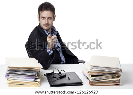 Portrait of a young businessman pointing towards camera while at work