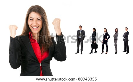 Portrait of a young businessman raising his hands in sign of victory with her team in background - stock photo