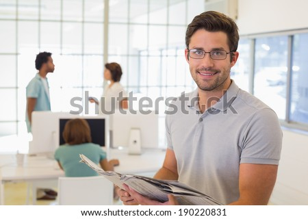 Portrait of a young businessman reading newspaper with colleagues in meeting in background at the office - stock photo