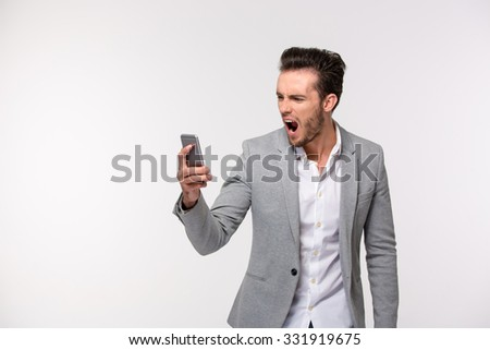 Portrait of a young businessman screaming on smartphone isolated on a white background - stock photo