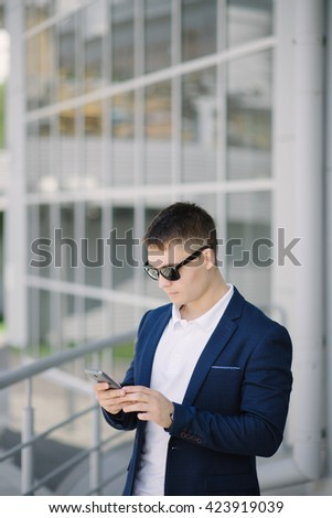 Portrait of a young businessman seeing on his smartphone on the street. Man with dark sunglasses. - stock photo