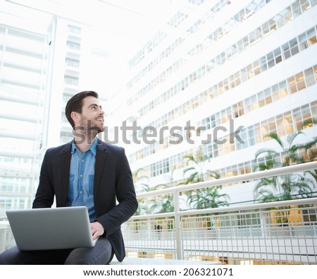 Portrait of a young businessman sitting with laptop inside building - stock photo