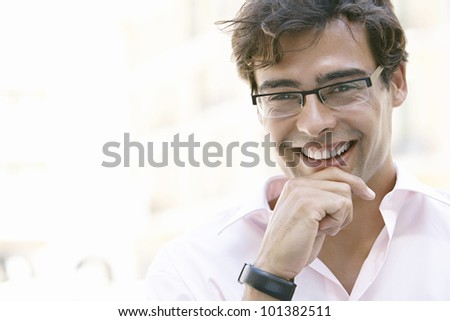 Portrait of a young businessman smiling at camera, holding his chin with his hand.