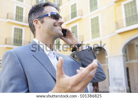 Portrait of a young businessman speaking on his cell phone in the financial district. - stock photo