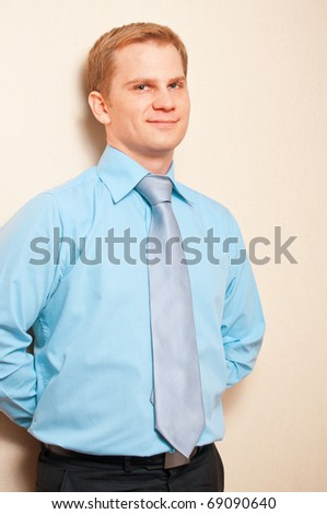 Portrait of a young businessman standing against wall - stock photo