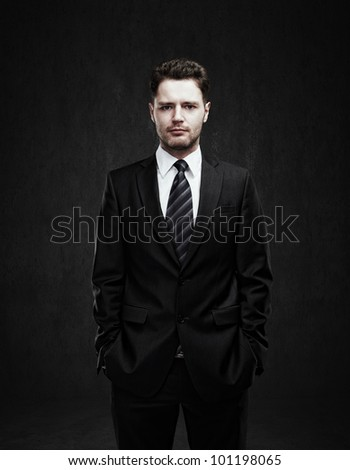 Portrait of a young businessman standing with his hands in the pockets. Young handsome man  looking confident. On a black background