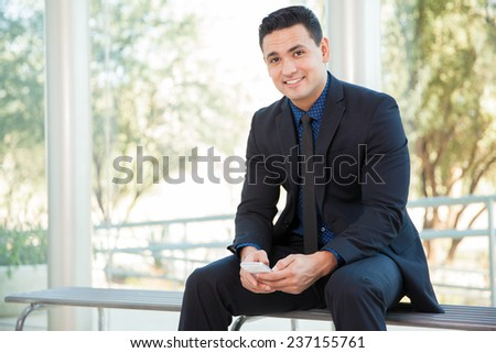 Portrait of a young businessman texting and social networking on his mobile phone and smiling - stock photo