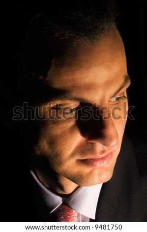 Portrait of a young businessman under dramatic lighting