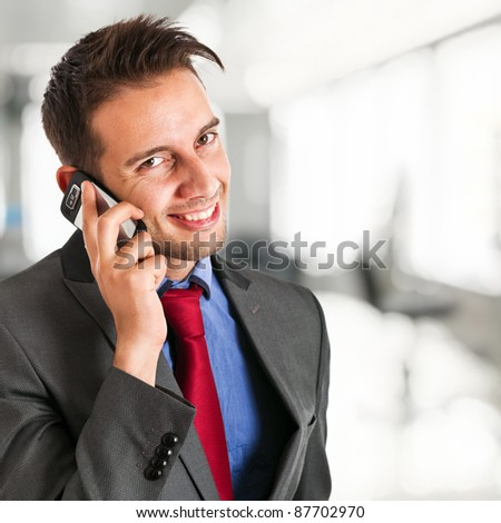 Portrait of a young businessman using a smartphone - stock photo