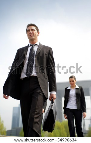 Portrait of a young businessman walking in the street - stock photo