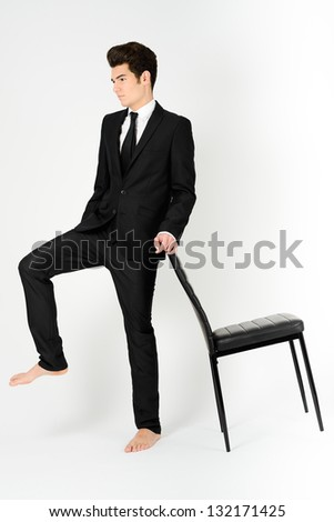 Portrait of a young businessman with a office chair, on white background - stock photo