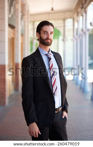Portrait of a young businessman with beard and formal suit standing outside - stock photo