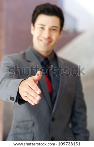 portrait of a young businessman with hand outstretched - stock photo