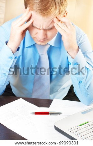 Portrait of a young businessman with headache - stock photo