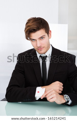 Portrait Of A Young Businessman With Playing Cards In Sleeve - stock photo